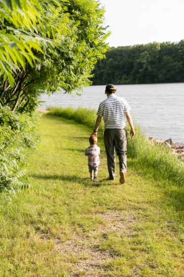father and son walking by a lake