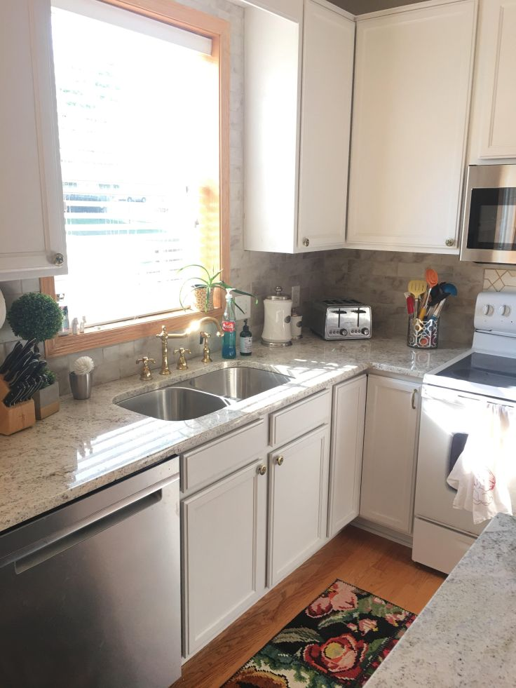 granite countertops with white kitchen and brass faucet.jpg